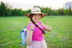 在逗人喜爱滑稽笑的画象或有背包和帽子的惊奇的妇女 免版税图库摄影