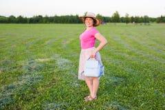 在逗人喜爱滑稽笑的画象或有背包和帽子的惊奇的妇女 免版税库存照片