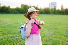 在逗人喜爱滑稽笑的画象或有背包和帽子的惊奇的妇女 库存照片