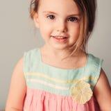 在逗人喜爱的微笑的儿童女孩淡色口气的方形的室内画象  免版税库存照片