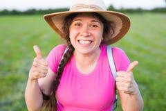 在逗人喜爱的滑稽的笑的妇女的画象有在显示赞许的帽子的雀斑的打手势 库存照片