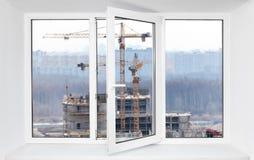 在通过打开的大声的建造场所噪声注入pvc窗口一个框架,看法 库存图片