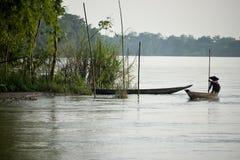 在通过滑动与船员的水的河船,有别的掩藏在竹子后 库存图片