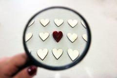 在通过透镜看的木心脏中的红色巧克力心脏 库存图片