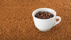 在速溶咖啡粒子床上的咖啡杯  库存照片