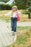 在遏制的女孩步行 牛仔裤,砰袋子 免版税库存图片