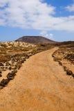 在道路和一座山的看法在海岛罗伯斯, Fuerteventu上 免版税库存照片