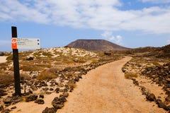 在道路和一座山的看法在海岛罗伯斯, Fuerteventu上 免版税库存图片