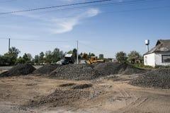 在道路施工工作期间,与空的桶的黄色装载者在石石渣站立 路的石头 免版税库存图片