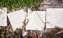 在道路的残破的水泥边路平板 免版税库存照片