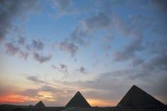在遥远的埃及金字塔后的日落 免版税库存照片