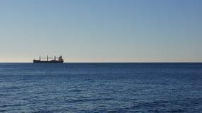 在遥远的天际的货船 免版税库存照片
