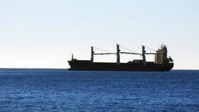 在遥远的天际的货船 库存照片
