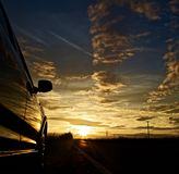 在遥远的日落与在左边的一辆停放的汽车 免版税图库摄影