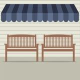 在遮篷下的空的木椅子 免版税库存图片