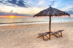 在遮阳伞之下的日落在海滩 免版税库存图片