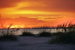 在那导致Sanibel和Captiva海岛从Ft的桥梁的发光的橙色日落 梅尔思海滩,佛罗里达 免版税库存照片