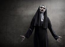 在邪恶的尼姑打扮的亚裔妇女 免版税图库摄影