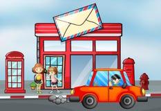 在邮局前面的橙色汽车 库存图片