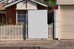 在郊区住宅物产之外的空白的房地产标志 库存照片