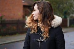 在郊区街道上的少妇佩带的冬天外套 图库摄影