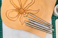 在部分被雕刻的皮革的各种各样的盖印的工具 图库摄影