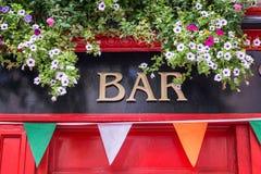 在都伯林爱尔兰禁止与花的标志和爱尔兰旗子颜色,爱尔兰客栈概念 免版税库存图片