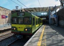 在都伯林Connolly驻地的箭电路轨火车在从Greystone的开往外地的旅途上通过Dunloaghair 免版税图库摄影