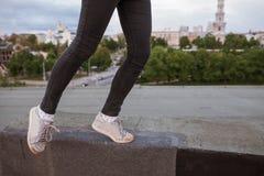 在都市城市背景的跳跃的腿 免版税库存图片