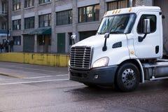 在都市城市街道上的中间半大小交付卡车 库存照片