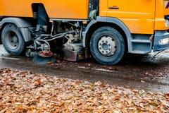 在都市城市街道清洁的卡车扫除机离开 图库摄影