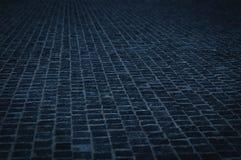 在都市夜修补石路面街道-与蓝色颜色口气的鹅卵石样式 免版税库存照片