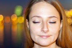 在都市夜空前面的满意的妇女 免版税图库摄影