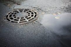 在都市沥青的圆的下水道人孔盖 库存图片