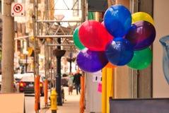 在都市街道上的五颜六色的气球 免版税库存照片