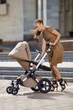 在都市街道上的时兴的现代母亲有摇篮车的。年轻m 免版税库存图片