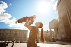 在都市街道上的时兴的现代母亲有摇篮车的。年轻m 免版税库存照片