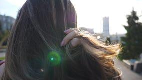 在都市街道和调直头发的无法认出的深色头发的妇女身分 在城市环境的女孩身分与 影视素材