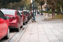 在都市街道边停放的汽车 免版税库存图片