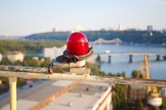 在都市风景背景的红色葡萄酒警报灯笼 库存照片
