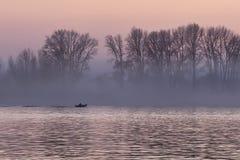 在鄂毕河的桃红色日落有一条浮动小船的 免版税图库摄影