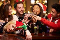 在酒吧分发的妇女在与朋友的圣诞节饮料期间 免版税图库摄影