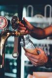 在酒吧啤酒的侍酒者倾吐的侍酒者倾吐的侍酒者倾吐的桶装啤酒在酒吧的酒吧啤酒 库存图片