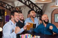 在酒吧尖叫的和观看的橄榄球,饮用的啤酒举行杯子,混合种族快乐的朋友的人小组 库存照片