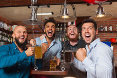 在酒吧尖叫的和观看的橄榄球,饮用的啤酒举行杯子,混合种族快乐的朋友的人小组 免版税库存图片
