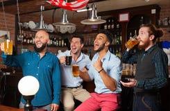 在酒吧尖叫的和观看的橄榄球,饮用的啤酒举行杯子,混合种族快乐的朋友的人小组 免版税图库摄影