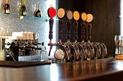 在酒吧柜台后的啤酒轻拍 库存图片