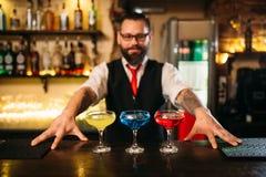 在酒吧柜台展示酒精coctails后的侍酒者 库存图片