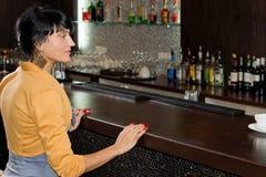 在酒吧柜台的少妇等待的服务 免版税库存图片