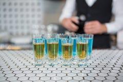 在酒吧柜台的杯蓝色盐水湖饮料和威士忌酒 图库摄影